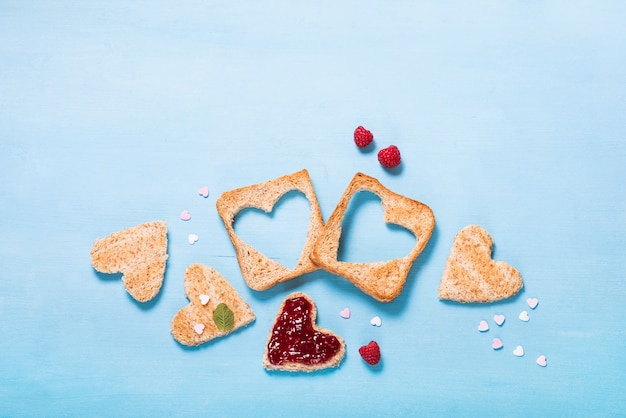 Saint valentine day background, heart shaped toast bread with raspberry jam on blue background, breakfast, romantic morning Premium Photo