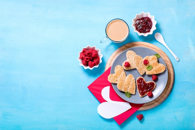 Saint valentine day background, heart shaped toast bread with raspberry jam and a cup of coffee on blue background Premium Photo