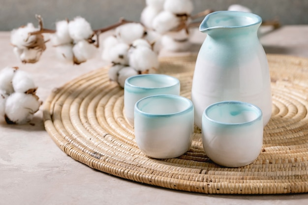 Sake ceramic set for traditional japanese with pitcher and three cups, standing on straw napkin with cotton flowers Premium Photo