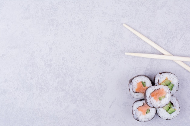Il sake maki rotola su sfondo grigio con le bacchette Foto Gratuite
