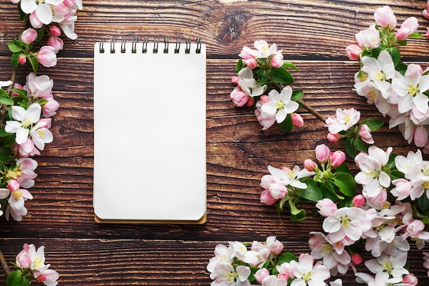 Sakura blossoms on dark rustic wooden background with a notebook. spring background with blossoming apricot branches and cherry branches Premium Photo