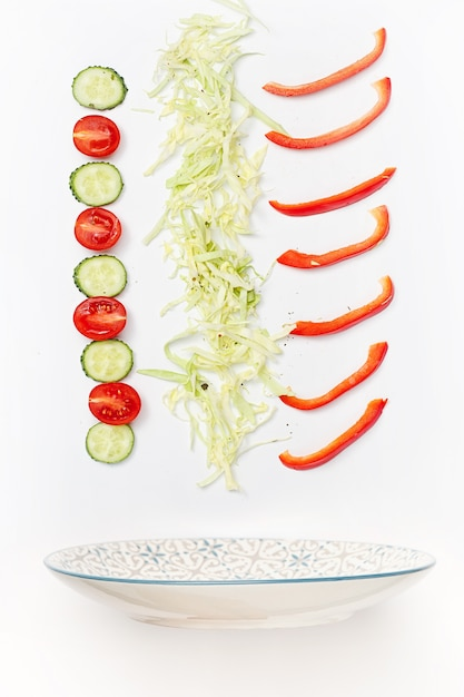 Salad bowl with falling vegetables Free Photo