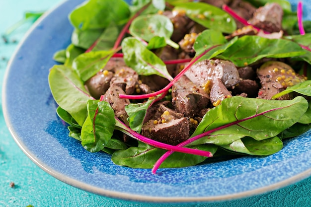 Salad of chicken liver and leaves of spinach and chard. Free Photo