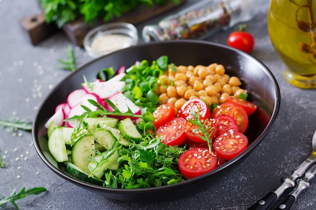 Salad of chickpeas, tomatoes, cucumbers, radish and greens. dietary food. buddha bowl. vegan salad. Free Photo