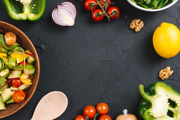 Salad and fresh vegetables on black concrete kitchen countertop Free Photo