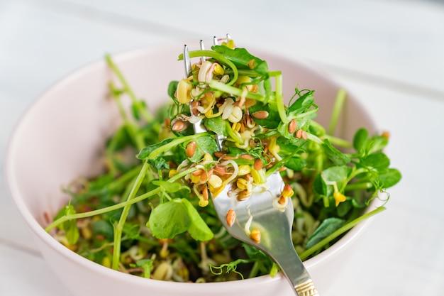 Салат из гороха с зелеными ростками и пророщенной фасолью в миске на сером Premium Фотографии