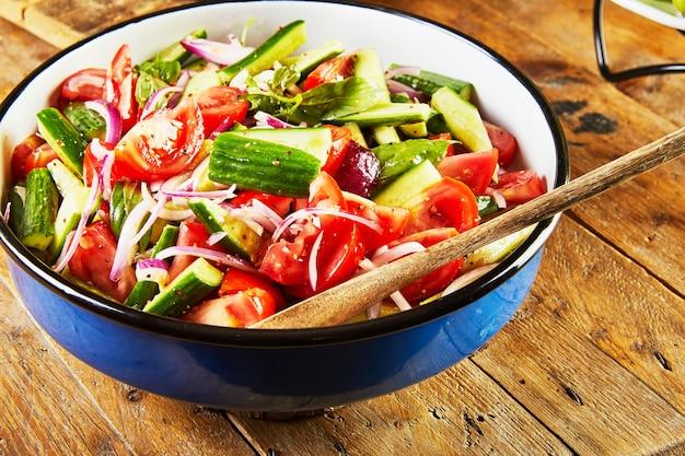 きゅうり、トマト、玉ねぎ、ハーブのサラダを木製のテーブルの青白のボウルに入れます。 Premium写真