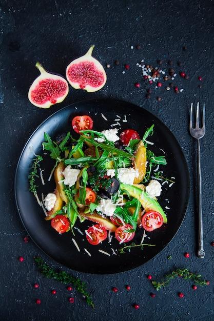접시에 샐러드 : Arugula, 체리 토마토, 흰색 무화과, 강판 치즈, 검은 포도 프리미엄 사진