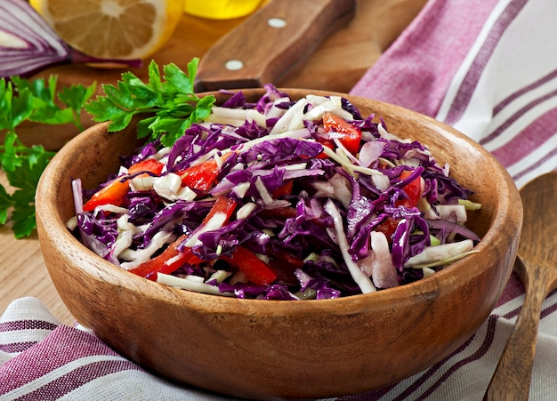 Salad of red and white cabbage and sweet red pepper, seasoned with lemon juice and olive oil in wooden bowl Free Photo