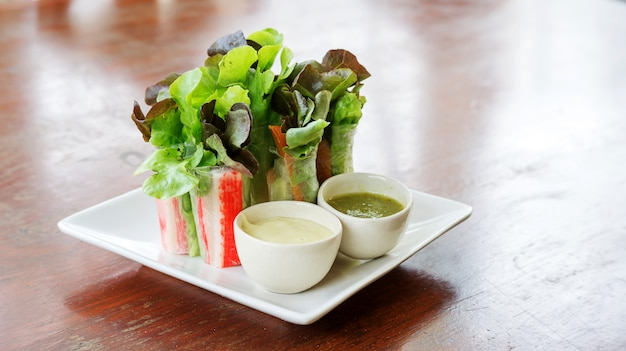 Salad roll and salad dressing on a white plate. Premium Photo