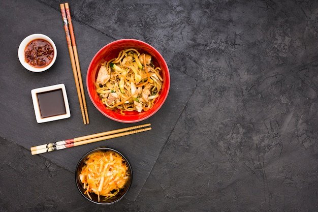 Salad; sauces and noodles served in bowl with chopsticks Free Photo