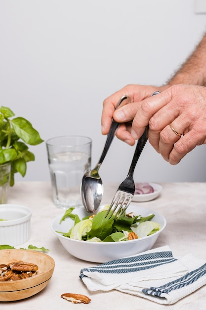 Salad tossing with walnuts and cloth Free Photo