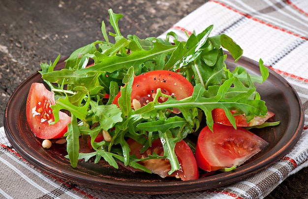 Salad with arugula, tomatoes and pine nuts Free Photo