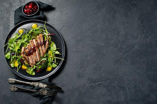 Salad with beef steak, arugula and chard on a black plate. Premium Photo