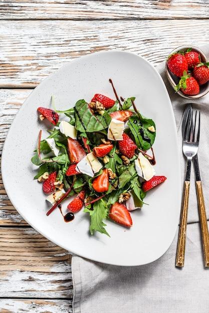 Салат с камамбером, клубникой, орехами, мангольдом и рукколой. белый фон. вид сверху. Premium Фотографии