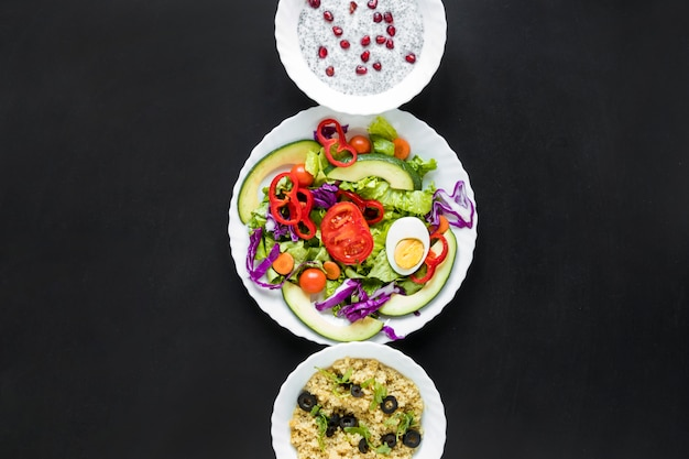 Salad with chia seed pudding and healthy oats arranged in a row Free Photo