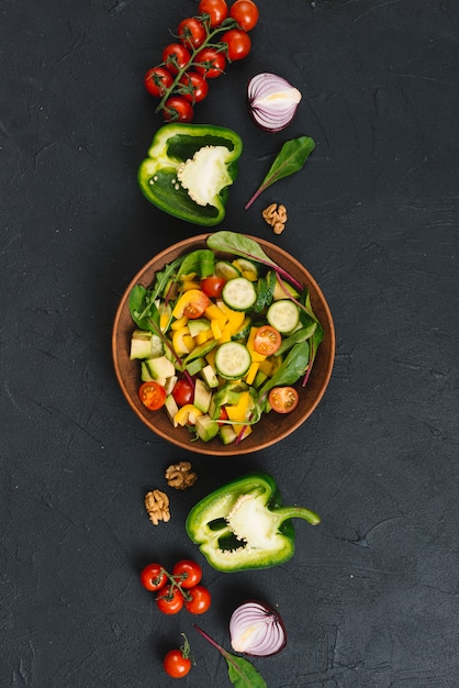 Salad with colorful vegetables on black kitchen counter Free Photo