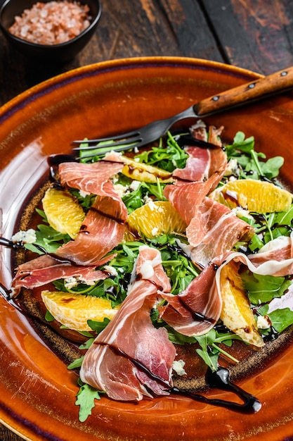 Salad with jamon ham, parmesan cheese, arugula and tangerine on a plate. dark wooden table. top view. Premium Photo