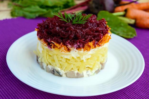 Салат со слоями вареных овощей и соленой рыбы Premium Фотографии