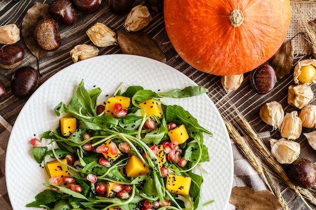 Salad with mango, roasted pumpkin, arugula, pomegranate seeds lying on white plate. Premium Photo