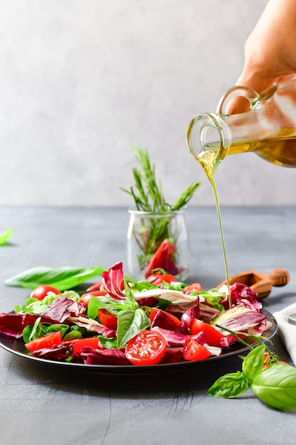 Salad with tomatoes and radicchio leaves, basil  with olive oil and rosemary. pouring olive oil Premium Photo