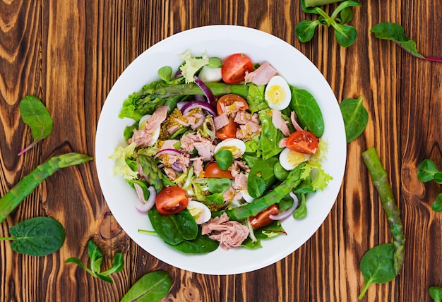 Salad with tuna, tomatoes, quail eggs, asparagus and onions on wooden Premium Photo