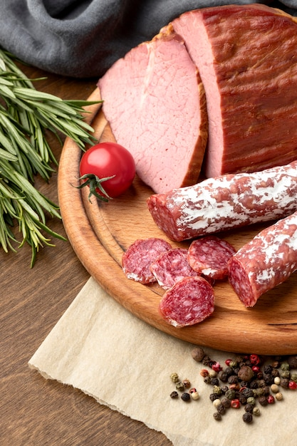 Salami and fillet meat on wooden board close-up Free Photo