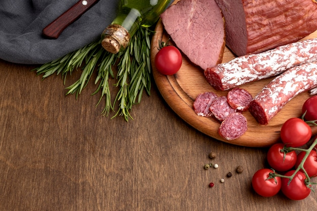 Salami and fillet meat on wooden board on desk Free Photo