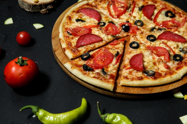 Salami pizza topped with fresh tomato and olive slices close-up view Free Photo