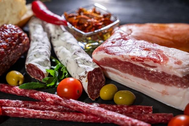 Салями, ломтики ветчины, колбаса, прошутто, бекон. мясо антипасто блюдо на деревянный стол. Premium Фотографии