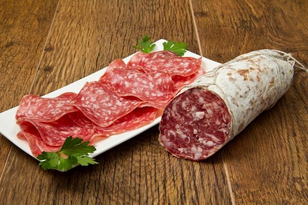 Salami sliced on wood background Premium Photo