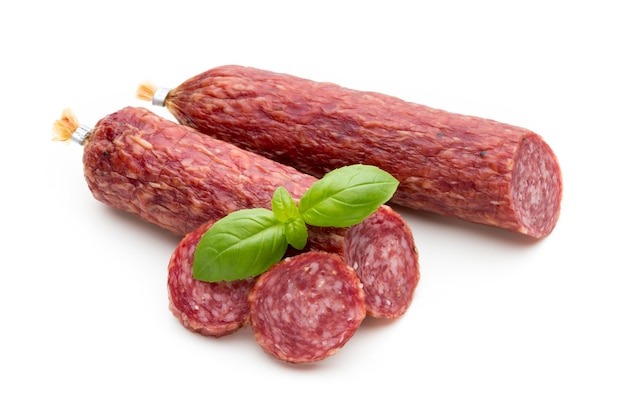 Salami smoked sausage, basil leaves and peppercorns isolated on white. Premium Photo