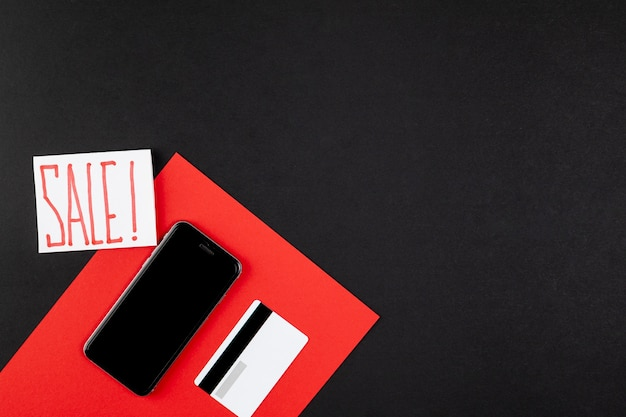 Sale ad next to credit card and phone mock up Free Photo