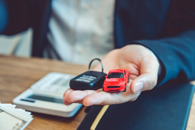 Sale agent giving car key to customer and sign agreement contract, insurance car concept. Premium Photo