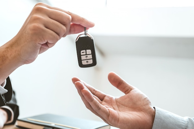Sale agent giving car key to customer and sign agreement contract, insurance car . Premium Photo