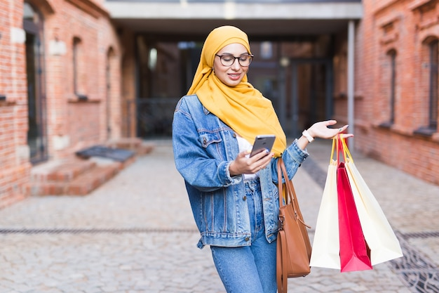 Sale and buying concept - happy arab muslim girl with shopping bags after mall holds mobile phone Premium Photo