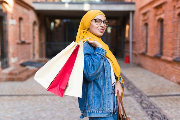 Sale and buying concept - happy arab muslim girl with shopping bags after mall Premium Photo