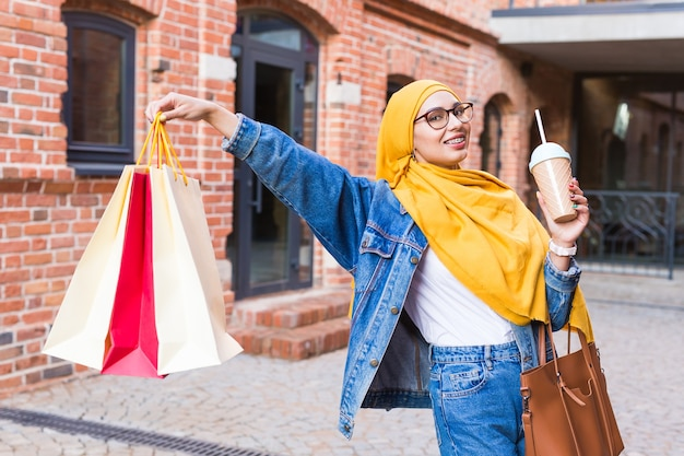 Sale and buying concept - pretty arab muslim girl with shopping bags after mall Premium Photo