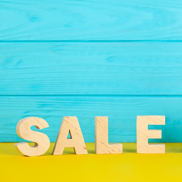 Sale lettering on blue wooden background Free Photo