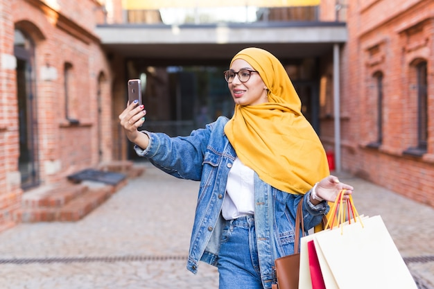 Sale, technologies and buying concept - happy arab muslim woman taking selfie outdoors after Premium Photo