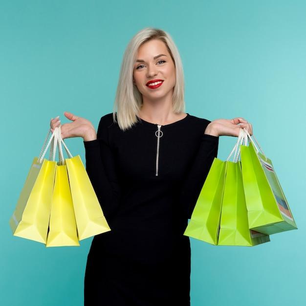 검은 금요일에 쇼핑백을 들고 판매 젊은 웃는 여자 프리미엄 사진