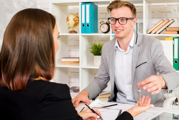 Sales agent giving keys to client Free Photo