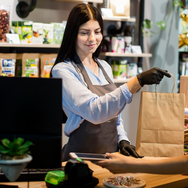Sales assistant handing out shopping bag to customer Free Photo