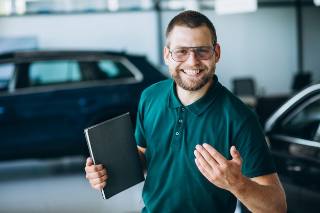 Sales man in a car showroom selling a car Free Photo