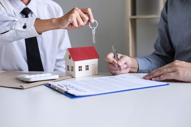 Sales manager giving keys to customer after signing rental lease contract of sale purchase agreement Premium Photo