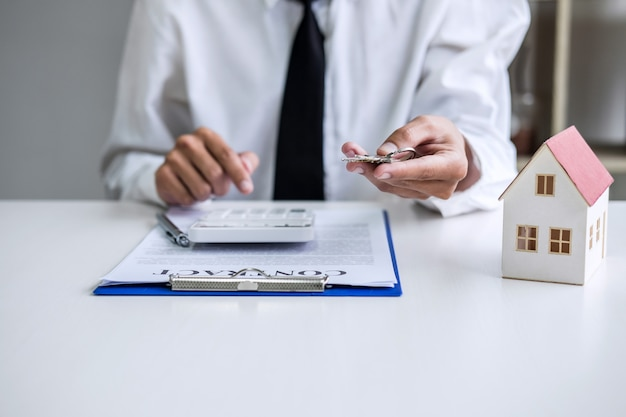Sales manager holding filing keys to customer after signing rental lease contract of sale purchase Premium Photo