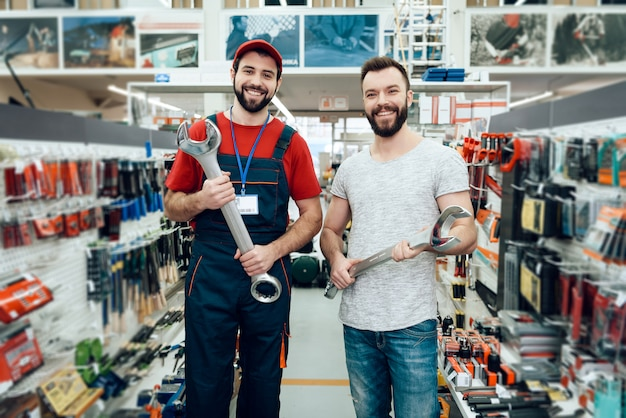 Salesman and buyer is holding new giant wrenches Premium Photo