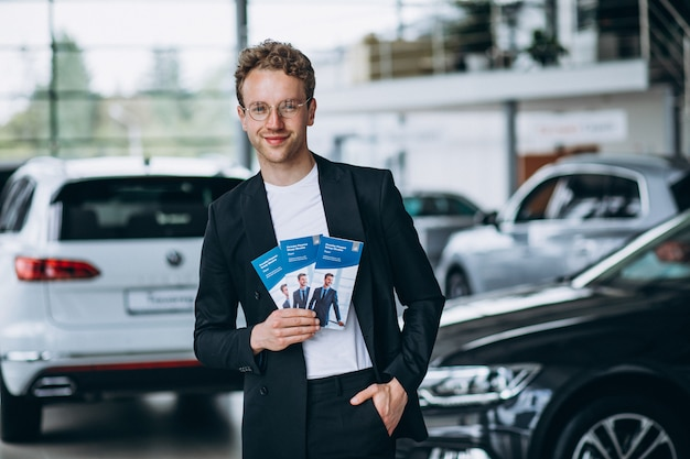 Salesman at a car showroom with business flyers Free Photo