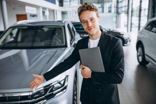 Salesman at a car showroom Free Photo
