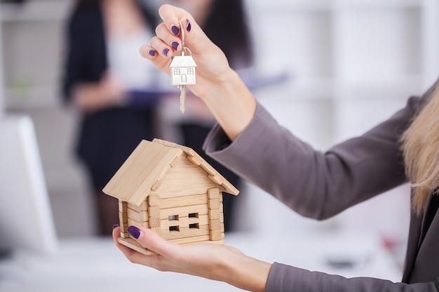 Продавец, несущий в руках образец дома, передает ключ от дома покупателю Premium Фотографии